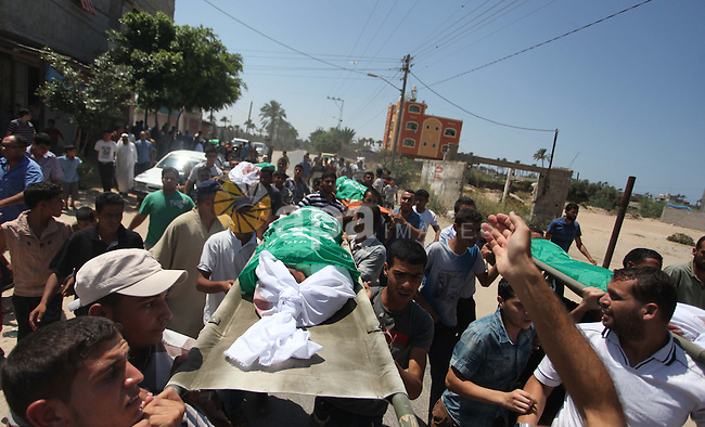 Palestinian relatives carry the bodies of members of the Alouh family, killed in an Israeli airstrike during their funeral in Deir al-Balah in the center of the Gaza Strip, on August 20, 2014. An Israeli air strike on a house in the Gaza Strip town of Deir el-Balah killed a pregnant woman, three young children and two male relatives, emergency services said. They named the dead as Rafat Aloah, 32, three of his children, his brother Mohammed 21 and the woman, Nabilah Aloah, whose relationship to the others was not immediately clear. Photo by Ashraf Amra