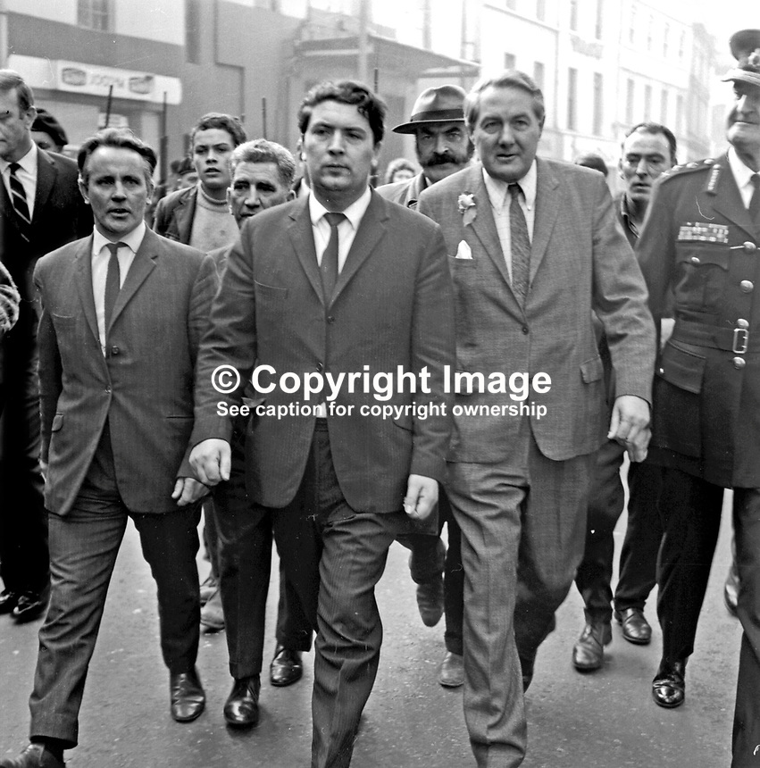 James Callaghan, UK Home Secretary, in William Street, Londonderry, N Ireland, UK, at the start of his visit to the Bogside to meet local residents. He is accompanied by Paddy Doherty, DCAC, left, John Hume, DCAC, and Sir Arthur Young, Commisioner of the City of London Police (right). Directly behind Doherty and Hume is Sean Keenan, DCDA. 19690827003<br />