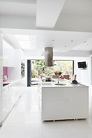 One of the best things about the kitchen is the reflections, from shiny doors to a glistening porcelain tiled floor, creating a room of three-dimensional quality