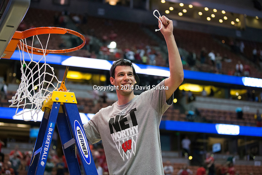 Wisconsin Badgers Duje Dukan cuts down a piece of the net after the Western Regional Final NCAA college basketball tournament game against the Arizona Wildcats Saturday, March 29, 2014 in Anaheim, California. The Badgers won 64-63 (OT). (Photo by David Stluka)
