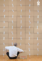 Businessman seated facing cardboard boxes wall (Licence this image exclusively with Getty: http://www.gettyimages.com/detail/109862332 )