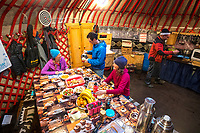Ski tourers at the dining table inside their yurt while on a ski trip in Kyrgyzstan