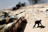 An rebel fighter crouches next to a tank being used in a battle between pro and anti Gadaffi forces near the town of Ajdabiya. On 17 February 2011, an uprising against the 41 year rule of Col Muammar Gadaffi started in eastern Libya..