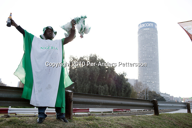 JOHANNESBURG, SOUTH AFRICA - JUNE 12: A Nigerian soccer fan stands with a green painted live chicken before a game between Nigeria and Argentina on June 12, 2010 outside Ellis Park stadium in Johannesburg, South Africa. Many Nigerian people reside in South Africa. Nigeria lost the game and didn't advance past the group stage in the 2010 World Cup, held in South Africa. In hosting the largest sporting event in the world, South Africa has a chance to impress the world with their country, hoping that the month long event will bring long lasting benefits for the country. (Photo by Per-Anders Pettersson)