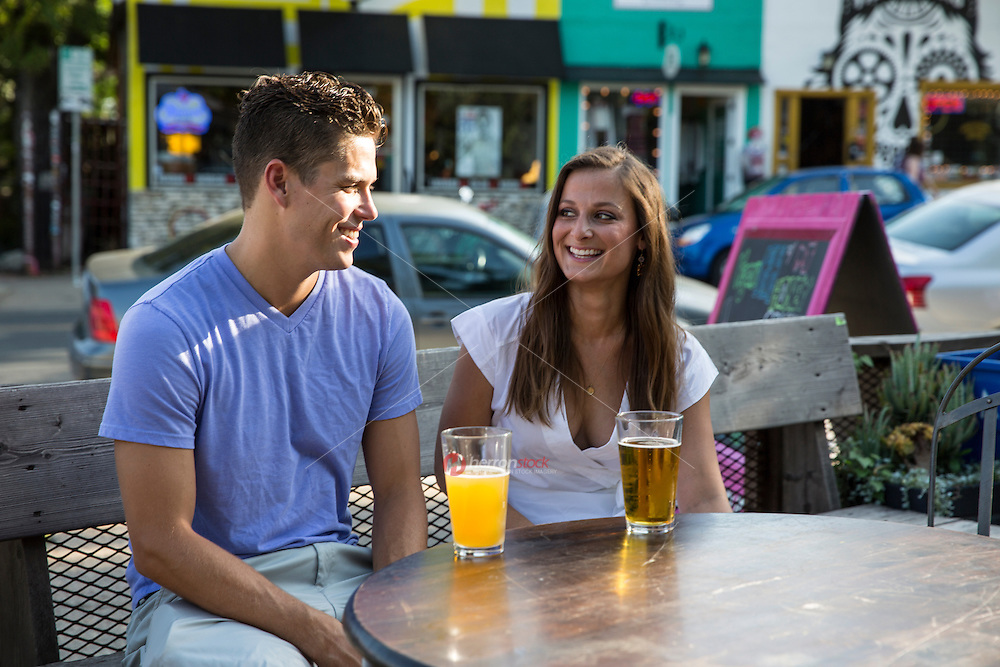 Attractive happy couple on a date drink beer in outdoor patio bar on East 6th Street in East Austin, Texas.