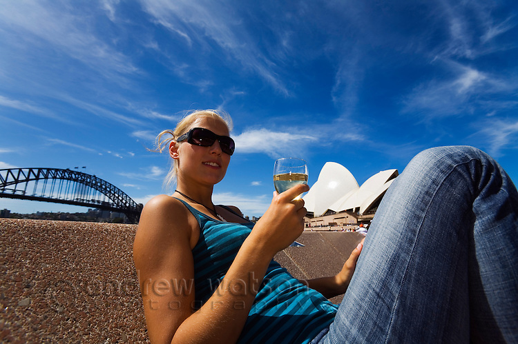 A woman enjoys a glass of wine at the Opera Bar on Sydney harbour.  Sydney, New South Wales, AUSTRALIA