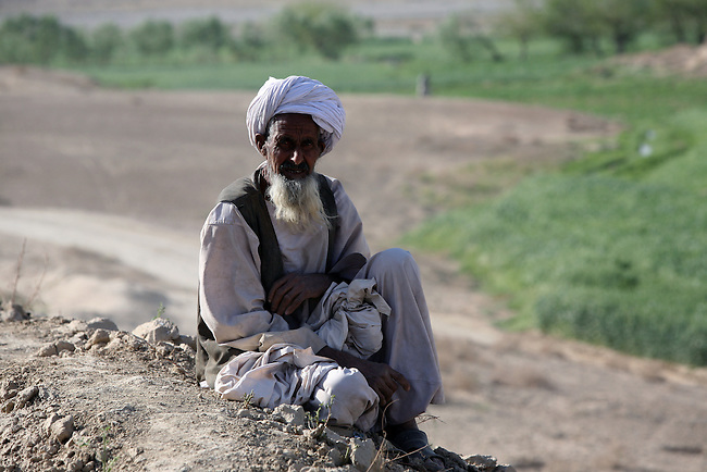 An old man sits on a hill overlooking a field on the outskirts of Delaram in Farah province, western Afghanistan. March 15, 2009. DREW BROWN/STARS AND STRIPES