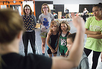 NWA Democrat-Gazette/CHARLIE KAIJO Eleora Robertson, 7, of Searcy and Teagen Loney, 7, of Van Buren (center) listen to coach Ashley Pagonis during a women's wrestling camp, Monday, June 3, 2019 at the Honey Badger Wrestling Club in Bentonville<br />