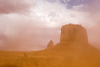 Wind-blown sand partially obscures Merrick Butte, right, and one of the easily-recognizable Mittens at the Monument Valley Navajo Tribal Park in southern Utah, Friday, March 10, 2006. The stunning vistas in the park, stars in many John Ford westerns, are an often-forgotten destination for American travelers. (Kevin Moloney for the New York Times)
