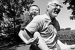 Photographer Jeff Miller plays with Leo, a 12-year-old orphan child from China, in Cottage Grove, Wis., during a summer photo session on June 17, 2016. Courtney and Donnie Henry are hosting the boy for a month as they advocate and strive to connect Leo with a forever family in the U.S. to adopt him. (Photo by Michelle Wahe)