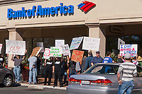 A man in a gray hat and striped shirt (far right of the frame) stands in front of a car watching the Occupy Orange County, Irvine protesters hold signs in front of a Bank of America in Irvine, CA on Saturday November 5.