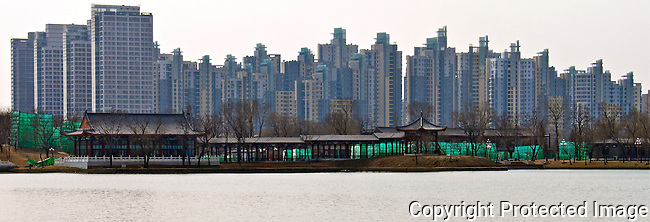 Magnetic capital apartments view across water park Tianjin Old chinese corridors with new modern buildings in the background photo