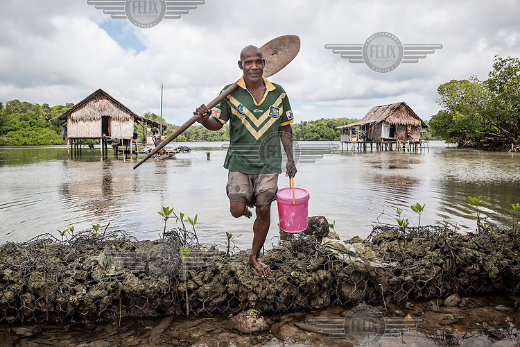 Mark Pokakes, 41, stands near his house in Bunai village on Pamachau Island. The only fresh water source on the island comes from rain. Pokakes is dressed in a shirt of the Australian rugy league team.