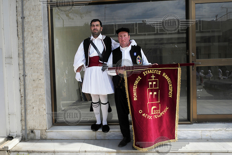 Men in the national Greek costume pose for a photo during celebrations for Greek Independence Day. Behind them is the empty window of a closed-down shop that has gone out of business.