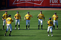 Michigan Wolverines players, including Blake Beers (29), Alec Rennard (19), Joe Pace (32), Brock Keener (35), Tommy Henry (47), Austin Batka (38), and Angelo Smith (40), stretch in the outfield during a game against Army West Point on February 17, 2018 at Tradition Field in St. Lucie, Florida.  Army defeated Michigan 4-3.  (Mike Janes/Four Seam Images)