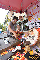 NWA Democrat-Gazette/FLIP PUTTHOFF <br /> FIRST FRIDAY ON THE SQUARE<br /> Dawn Setters of Bella Vista arranges hand-sewn fabric wreaths and other at her exhibit tent on Friday Sept. 7 2018 during the First Friday event downtown Bentonville. The area around the square becomes a community party with a different theme the first Friday of each month with food, art and live music. Setter makes clothing, Halloween costumes, wreaths and other items she sells through her business, &quot;Ozark Mountain Gypsy.&quot;