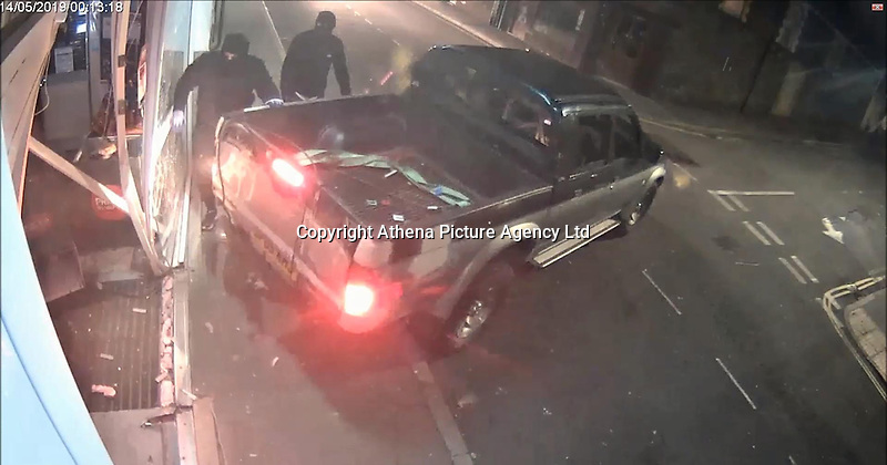 """Pictured: CCTV still showing a Mitsubishi 4x4 crashes against the front of the Co-op store in Treharris, Wales, UK. 14 May 2019<br /> Re: Blundering ram raiders who escaped with an ATM machine containing £80,000 unaware it was fitted with a secret tracking device, have been jailed for a total of twenty years by Merthyr Tydfil Crown Court.<br /> The masked gang took the cash machine to a deserted farmhouse where a security monitoring company picked up its GPS signals.<br /> The money was being """"divvied up"""" when police swooped to arrest the five gang members and seize a bin bag packed with £20 and £10 notes<br /> A jury was shown dramatic video of the gang reversing a 4X4 vehicle into a Valleys Co-op store in the early hours.<br /> Prosecutor Alex Greenwood said: """"The peace of Treharris village was interrupted by an audacious criminal enterprise.<br /> """"It was a highly-organised burglary to remove the ATM from the Co-op store.<br /> """"A masked criminal gang reversed a Mitsubishi pick-up into the front of the shop. <br /> """"Straps were attached to the machine and the pick-up drove off dragging it down the street with sparks flying off it."""