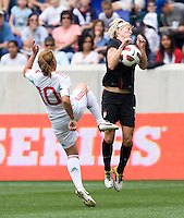 Megan Rapinoe (15) of the USWNT  tries to protect herself as Dinora Garza (10) of Mexico clears the ball into her body during the game at Red Bull Arena in Harrison, NJ.  The USWNT defeated Mexico, 1-0.