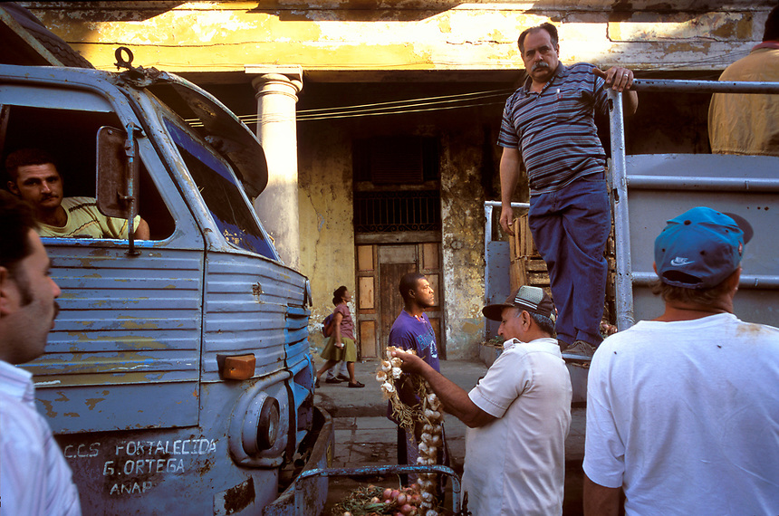 Buyers and sellers browse garlic and other wares brought in by truck to a morning produce market in Old Havana.