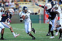 30 October 2010:  FIU running back Kedrick Rhodes (9) attempts to evade Florida Atlantic linebacker Randell Johnson (15) in the first quarter as the Florida Atlantic University Owls defeated the FIU Golden Panthers, 21-9, at Lockhart Stadium in Fort Lauderdale, Florida.