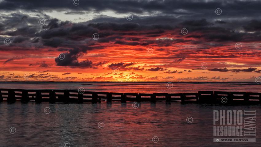 Fiery sunset over Kane'ohe Bay, with a man-made structure in the foreground, Kualoa Regional Park, Kane'ohe, O'ahu.