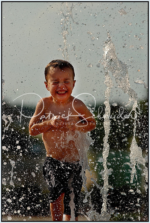 A young boy runs through the water spraying up at a community water park. Image is model released.