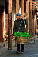 Man carrying produce in the water town of Zhouzhuang, China