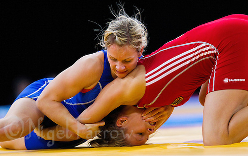 11 DEC 2011 - LONDON, GBR - Laura Skujina (LAT) (in blue) tries to overpower Aline Focten (GER) (in red) during their women's 63kg category bronze medal bout during the London International Wrestling Invitational and 2012 Olympic Games test event  at the ExCel Exhibition Centre in London, Great Britain .(PHOTO (C) NIGEL FARROW)