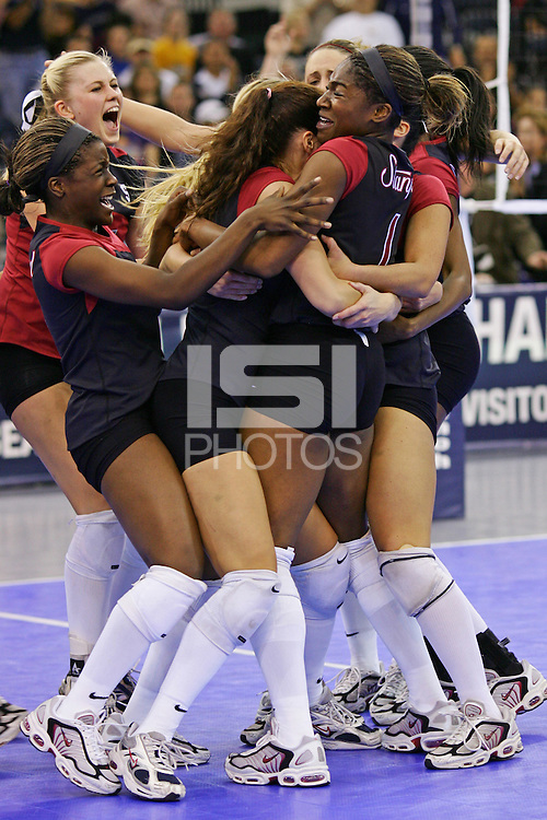 18 December 2004: Stanford's Courtney Schultz, Njideka Nnamani rush the court as Jennifer Hucke hugs Ogonna Nnamani after match point during Stanford's  30-23, 30-27, 30-21 victory over Minnesota in the 2004 NCAA Women's Volleyball National Championships in Long Beach, CA. Stanford won their sixth women's volleyball title in school history.<br />