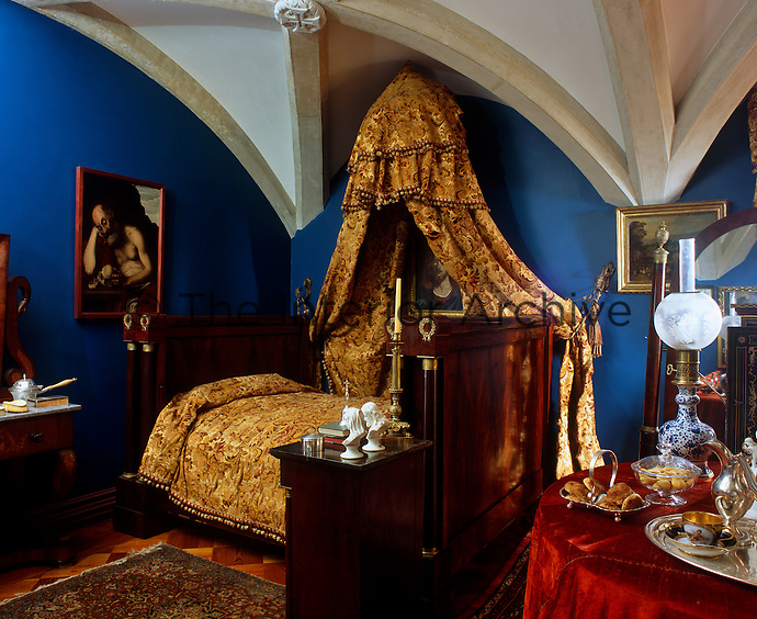 Golden yelllow damask drapes hang from a corona above an Empire bed in this masculine cobalt blue bedroom