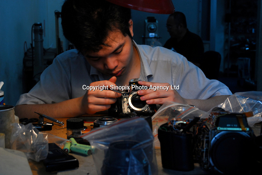 A man repairs a camera in Guangzhou, China.  ....