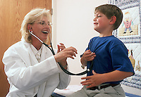Female pediatrician has fun with young patient during an office visit.