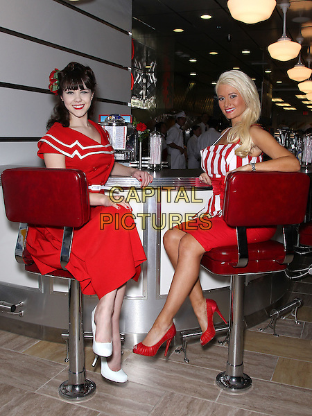 CLAIRE SINCLAIR & HOLLY MADISON.at the ribbon cutting of the opening of Johnny Rockets at the Flamingo Las Vegas, Las Vegas, Nevada, USA, 10th December 2010..full length sitting red and white striped top  dress skirt shoes diner .CAP/ADM/MJT.© MJT/AdMedia/Capital Pictures.