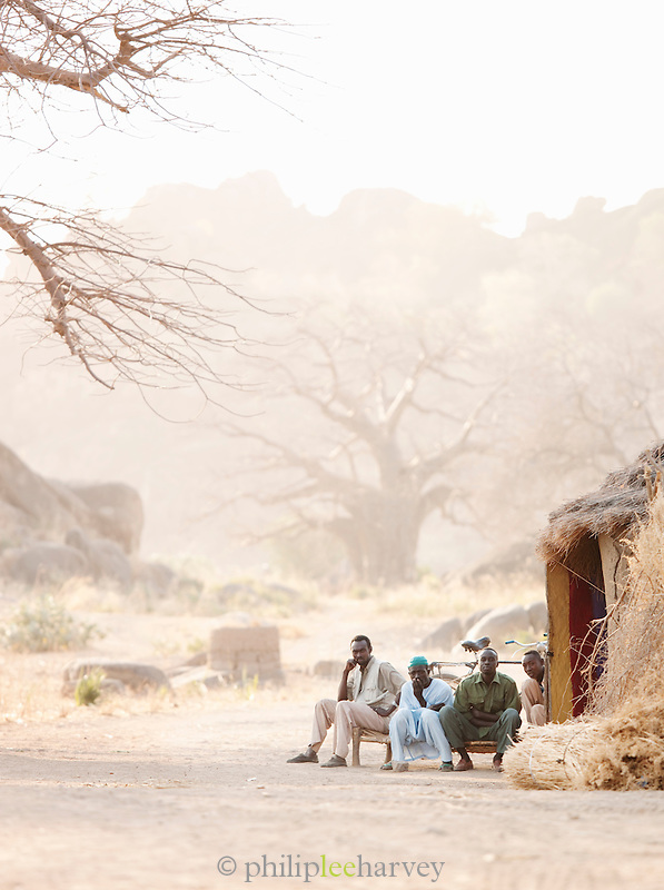Men of the Nuba tribe sit outside a mud hut in the village of Nyaro, Kordofan region, Sudan