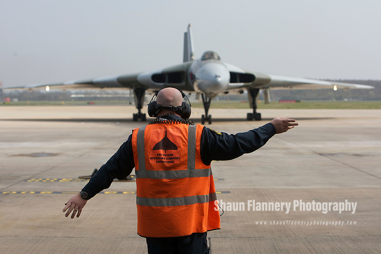 Pix: Shaun Flannery/shaunflanneryphotography.com...COPYRIGHT PICTURE>>SHAUN FLANNERY>01302-570814>>07778315553>>..29th March 2011..............The last flying Vulcan, XH558,  touches down at Robin Hood Airport Doncaster Sheffield. .Vulcan XH558 is to spend the summer based at the airfield where she once stood on Quick Reaction Alert during the Cold War..A Vulcan Operating Company Engineering 'ramp agent' directs the aircraft..
