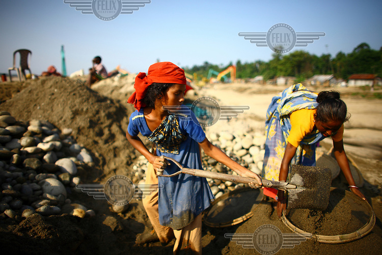Women and children work sifting sand at Bhollar Ghat. At least 10,000 people, including 2,500 women and over 1,000 children, are engaged in stone and sand collection from the Bhollar Ghat on the banks of the Piyain river. Building materials such as stone and sand, and the cement which is made from it, are in short supply in Bangladesh, and commands a high price from building contractors. The average income is around 150 taka (less than 2 USD) a day..