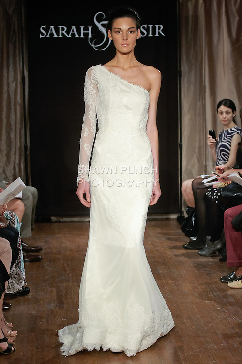 """Model walks runway in an Aimee Bridal dress - one sleeve fitted mermaid lace gown, by Sarah Jassir, for the Sarah Jassir Spring 2013 """"La Reve: The Dream"""" collection, during Bridal Fashion Week New York."""