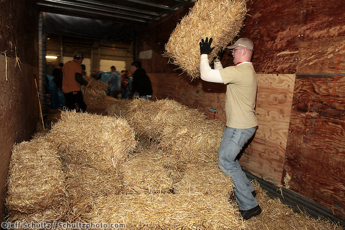 Tom Kohnke unloads a portion of the1500 bales of straw from a shipping container at Airland Transport in Anchorage to be sent out to the 22 checkpoints along the Iditarod trail Thursday, Feb. 7, 2013.