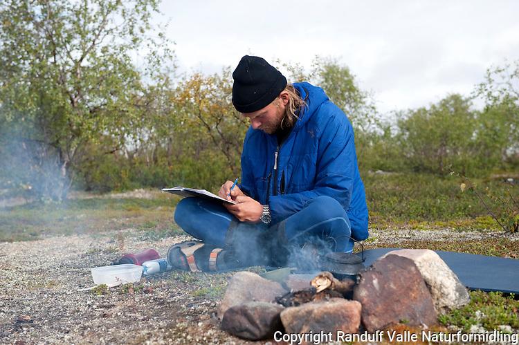 Mann sitter ved bål og skriver dagbok. ---- Man sitting by camp fire.