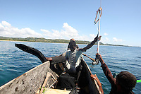 Sera, 32 years old, married and father of 3 boys, is about to get into the water on a reef around Anaratavo bay, north to Manompana village. Maro, his diving buddy, gives him the spear gun they share. Madagascar, 2012.