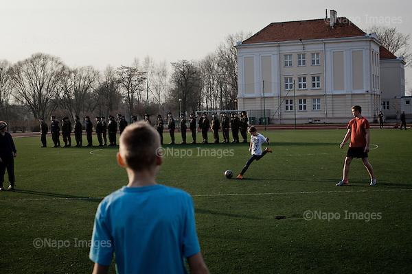 KALISZ, 7/03/2015:<br /> Cwiczenia z replikami broni na szkolnym boisku. W ten weekend czlonkowie organizacji zebrali sie w lokalnym liceum ogolnoksztalcacym na dwudniowe cwiczenia. Od rozpoczecia wojny na Ukrainie rozne organizacje paramilitarne staja sie coraz bardziej popularne.<br /> Fot: Piotr Malecki<br /> <br /> KALISZ, POLAND, MARCH 7, 2015:<br /> Kids play football as young members of &quot;Strzelec&quot; (&quot;The Shooter&quot;) paramilitary association and of local classes with military profile, are having their training at the sports grounds of the local school. This weekend a few paramilitary groups from this region of Poland are having their trainining session, their base being a secondary school number 5 in Kalisz.<br /> Since the start of war in Ukraine, paramilitary associations are becoming more popular.<br /> (Photo by Piotr Malecki)