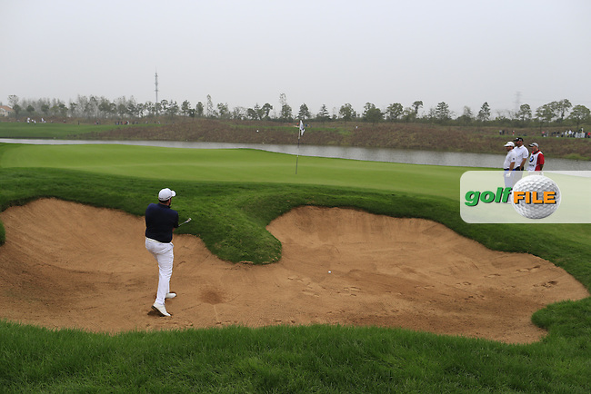 Shane Lowry (IRL) chips from a bunker at the 17th green during Saturay's Round 3 of the 2014 BMW Masters held at Lake Malaren, Shanghai, China. 1st November 2014.<br /> Picture: Eoin Clarke www.golffile.ie