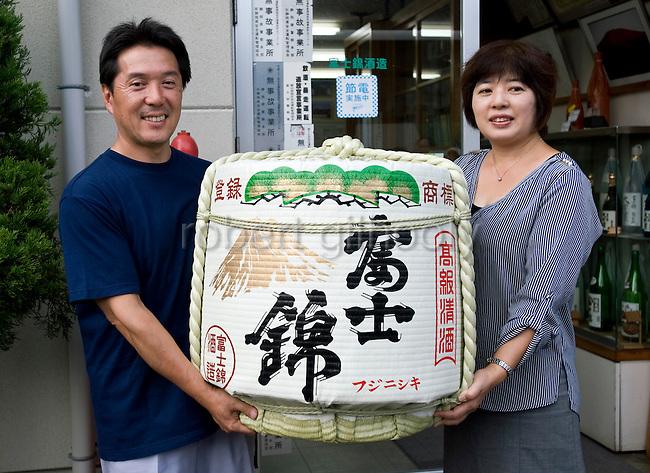 Shinichi Sei, president of Fuji-nishiki Sake Brewery, and his wife Tomoko stand with a cask of the company's sake at the brewery in Fujinomiya, Shizuoka Prefecture Japan on 02 Oct. 2012.  Photographer: Robert Gilhooly