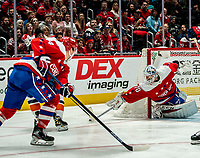 WASHINGTON, DC - JANUARY 31: Braden Holtby #70 of the Washington Capitals  pushes the puck clear of his net during a game between New York Islanders and Washington Capitals at Capital One Arena on January 31, 2020 in Washington, DC.