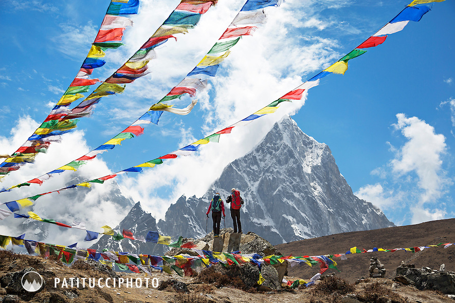 Hikers stand in front of Cholatse with prayer flags above, Khumbu Valley, Nepal.