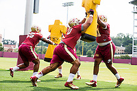 TALLAHASSEE, FLA.8/6/13-FSU080613CH-Florida State's Jacob Fahrenkrug, center, blasts into Bobby Hart, right, during the Seminole's first day of practice Aug. 6, 2013 in Tallahassee, Fla.<br /> <br /> COLIN HACKLEY PHOTO