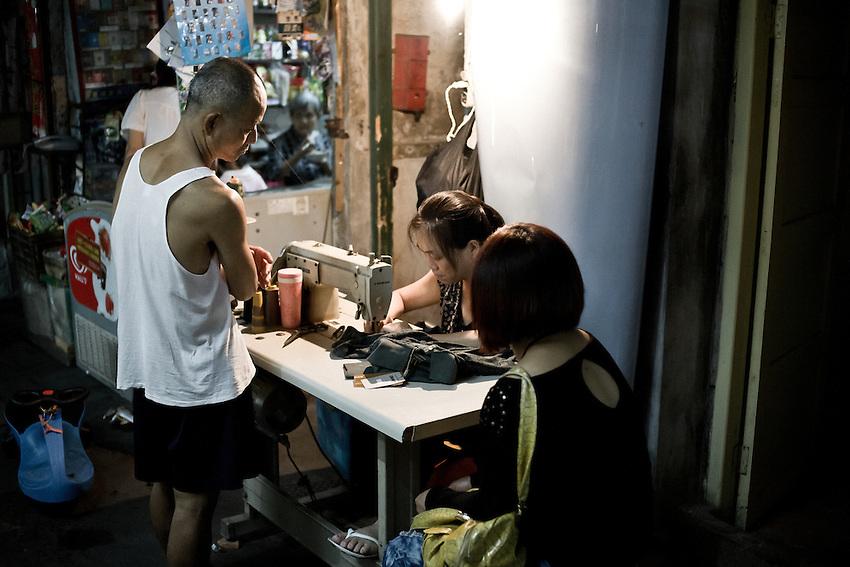 Une couturière travaille dans la rue, devant ses clients. Les ruelles du centre de Xiamen (Amoy) sur la rive d'en face ont gardé leur rythme animé à la tombée du jour.