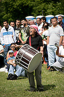 Turkish woman playing the davul drum for folkdancers at the Day-Mer Festival 2009 at Clissold Park, Hackney, London, UK