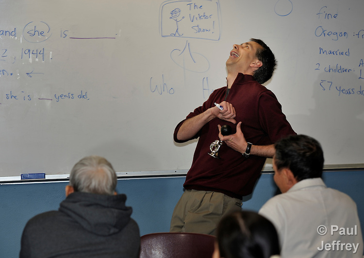 Instructor Christian Jensen fakes a heart attack in response to a student's answer during an English as a second language class at Tacoma Community House in Tacoma, Washington.