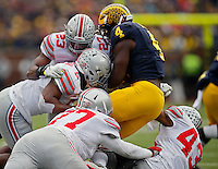 Ohio State Buckeyes safety Tyvis Powell (23) and linebacker Raekwon McMillan (5) come together to tackle Michigan Wolverines running back De'Veon Smith (4) in the 2nd quarter at Michigan Stadium in Arbor, Michigan on November 28, 2015.  (Dispatch photo by Kyle Robertson)